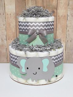 2 Tier Mint & Grey Elephant Mini Diaper Cake Use as a baby shower centerpiece, gift table decoration or have it sent directly to the recipients as a unique and practical welcome baby home gift. Ingredients: ** 28 - Pampers Swaddlers (size 1) ** 100% usable diapers ** Cute Baby
