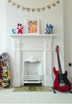 Victorian fireplace. Bunting, robots, guitar and skateboard. Boy's room.