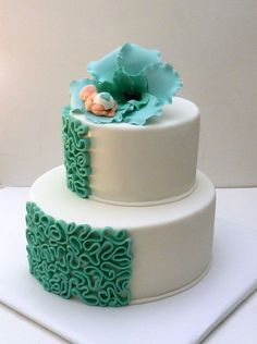 A little one rests inside a teal colored blossom atop this cake....a great Baby Shower Cake... cakecentral.com