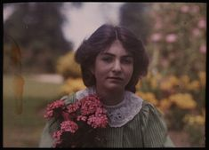 An autochrome of her daughter in a garden, holding a brightly coloured bunch of pink flowers, taken by Etheldreda Janet Laing. In the summer of 1908 Laing took a series of autochrome portraits of her children in the garden of the family home, Bury Knowle
