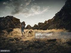 Stock Photo : A man walking through grass and rocks.