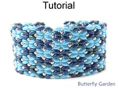 "Butterfly Garden SuperDuo Bracelet Downloadable Beading Tutorial #18058  We couldn't decide whether this lovely design looked more like a mass migration of butterflies or a garden of flowers - then we realized, it's a Butterfly Garden!  This substantial design measures approximately 1¼"" wide and has an adjustable closure for a perfect fit.  With over 90 high resolution full-color photos and easy to follow step-by-step directions, youll have fun stitching up this cheerful bracelet that's…"