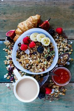 Diet breakfast set - Delicious breakfast set. Healthy muesli with banana, nuts, linseeds, fresh berries and figs, coffee, croissant, fruit jam over rustic wooden backdrop. Top view, flat lay