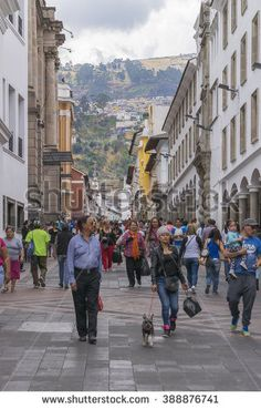 QUITO, ECUADOR, OCTOBER - 2015 - Crowded sidewalk with colonial style buildings and hill at background in the historic center of Quito, Ecuador.