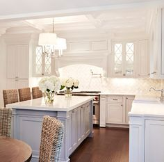 """Chango & Co., Cabinet paint color is Benjamin Moore Frostine AF-5. Island: """"Benjamin Moore Coventry Gray HC-169"""". Countertop is Caesarstone – white quartz."""
