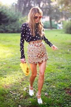Anna dello Russo. Pattern clashing with a very cute Dolce & Gabanna star print shirt, red sunglasses and a skirt with gems.