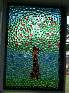 My apple tree faux stained glass window.  Used an old window, flat glass marbles and pieces from a broken wine bottle for the trunk.   Cover the whole thing with an epoxy gloss coat (comes in a two part kit).  Kits cost about $25 at Home Depot and Lowe's.  A one quart kit can cover about 6 square feet.  I did not glue the marbles to the glass first.  Just laid them on the glass.  Darker marble colors look best.  This is even better in person IMHO.  :)