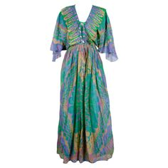 Silk gown from Zandra Rhodes featuring an iconic tribal inspired motif. Mustard yellow, pinky lilac and blue violet organic patterns are screened on a grass green ground. Signature pleating trims a plunging lace up neckline that's decked with iridescent pink flower sequins. Flutter sleeves extend from elasticized waistband   United Kingdom, 1970's
