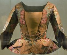 Casaca, (Dress coat), 1730-1740, Silk brocade jacket in green with polychrome floral decoration. Long to the hip, cut at the waist and pleats on the sides which start from a button. The skirts are decorated with pockets portfolios. The sleeve, with around three quarters triangular.  Museo del Traje  © Ministerio de Educación, Cultura y Deporte