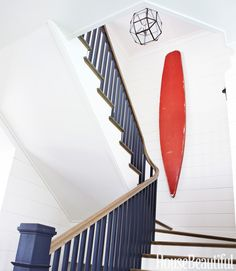 A vintage surfboard plays up the generous height of the upper stairwell. The rails are painted the same color as the kitchen cabinets.   - HouseBeautiful.com