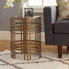 Stage a stylish lamp or family of framed photos atop this wrought iron end table, featuring an openwork design, a gold finish, and removable glass top.