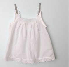 Sew a super sweet and delicate Lacey Trimmed Girl's Blouse with this free sewing pattern. This simple shirt is easy to make for any skill level, and the delicate lace trim adds a sweet innocence to this straightforward pattern. Sewing Patterns For Kids, Clothing Patterns, Sewing Ideas, Couture Bb, Blouse Tutorial, White Lace Blouse, Eyelet Lace, Sewing Blouses, Sewing Kids Clothes