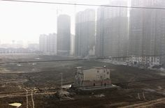 A nail house sits surrounded by a ditch at a construction site for a new residential compound in Xiangyang, Hubei province, on November 19, 2013. The family living inside had refused to move out due to a disagreement over their compensation plan, local media reported.