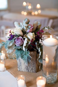 Rustic and elegant wedding centerpiece with dusty miller, roses, and candles