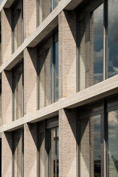 Buff brick rhythmic facade with depth and shadow and contrasting dark window frames