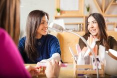 Female friends hanging out at a nail salon stock photo