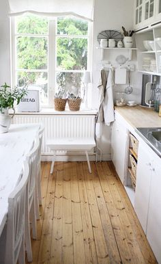 All white country kitchen + honey wood floors; would change out countertop for a different finish.