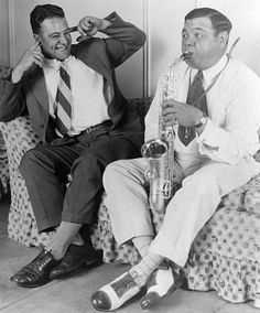 Lou Gehrig protects his ears as Babe Ruth blows his horn