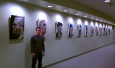 Mr. Schoenhofer next to his art being featured at a sports center.