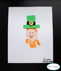 Handprint Leprechaun. → Materials: orange paint, peach paint, paint brush, paper, green and black craft foam, scissors, glue, yellow button, and sharpie.