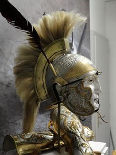 Roman parade helmet (recreation) with horsehair plume and goose feathers, silvered, with brass applique, and matching greaves.