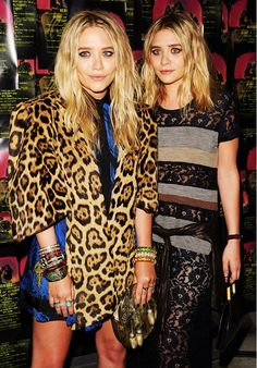 Mary-Kate and Ashley Olsen wear a cheetah print outerwear with stacked bracelets and an allover lace, striped outfit with a metallic shirt tied around the waist.