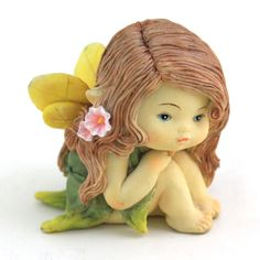 A wee little fairy resting her head upon her knees.