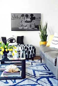 Black and white living room with hints of yellow and vintage Mickey Mouse on TV screen
