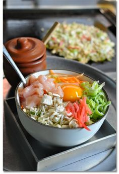 Okonomiyaki (prepared version shown in the background) is a Japanese dish that is a similar to a pancake, but with a LOT of ingredients mixed into the batter.