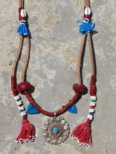 Kinship Stories: The base of this necklace is made with genuine Egyptian leather. The silver centerpiece is vintage Nepali. It is made of sterling silver (925k), coral and turquoise. The long tassels are Uzbek and come from a traditional wall hanging while the short blue ones are rural Egyptian. The various glass beads are Afghani. The necklace is entirely handmade and is a one-of-a-kind piece.
