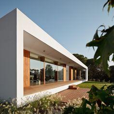 Fachada acristalada + porche. Mezcla de madera y blanco.