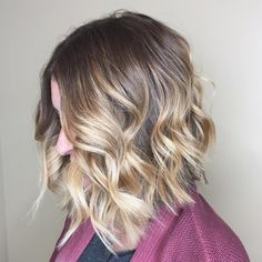 A layered, wavy lob is the perfect short haircut to show off this pretty blonde balayage by Aveda Artist Gabby.