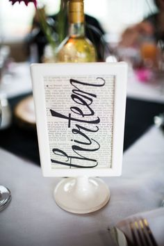 Table numbers written on book pages, framed for a nice touch
