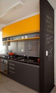 A mistura do azulejo na parede com a marcenaria amarela deixou a cozinha com um ar retrô