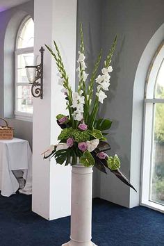 simple bold contemporary flower pedestal arrangements.  Gladiolus, anthiriunum…