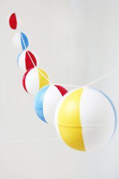 DIY Pool Party Beach Ball Garland ~ lightweight styrofoam balls painted in red, yellow, & blue | tutorial from Studio DIY