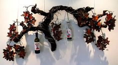 Maclaren Vale artwork # dailyshoot Adelaide Australia  Taken in the visitor centre of Maclaren Vale Australia where there is a great little art gallery. Loved the wine botles hanging off the vine, but was attracted by the shadows that were made and the problems of exposure. Camera set to aperture setting and handheld exposed for the white background.