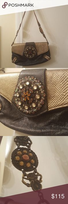 """Leatherock Purse Shoulder Leather Swarovski Europe This beautiful purse is made with the finest European leather and adorned with genuine stones. It is dark in color with a magnetic closure and one slip pocket. It is in excellent condition.  *The thread is slightly loose at the corner of the slip pocket. It has a pin hole from a price tag and two very small spots on the interior from storage. They can be wiped lightly. (see pic 5 & 6) The interior is like new and never used.  Length 6"""" Width…"""