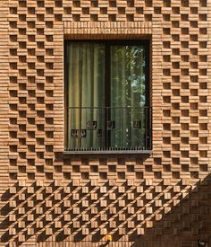 boozhgan architecture studio sculpts a dynamic brick facade for the haghighi house