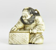 Netsuke of carved ivory, Zhong Kui (J: Shoki) the demon-queller seated, sharpening a sword on a whetstone: Japan, by Tomotoshi, 19th century
