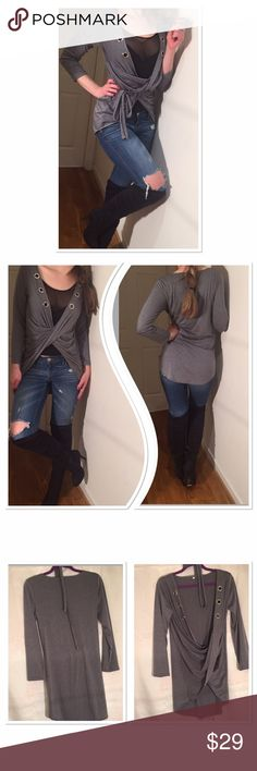 """New boutique high low wrap gray shirt with belt Perfect shirt for layering! Super cute design high low and wrap around upfront. Stylish detail - metal circles down the neckline. Can be worn with or without belt ( included) I like it with jeans but will look good with mini and boots as well Size M ( purchased from Turkish boutique that's why specified as L) measurements: pit to pit- 19"""" length upfront 16"""" back 31"""". Material - polyester, manufactured in Turkey- not specified on the label…"""