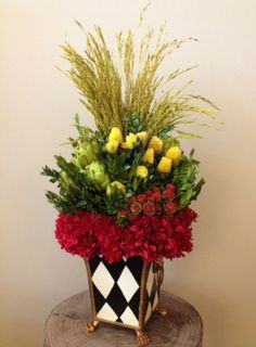 Custom Dried Floral Arrangement in harlequin cache pot including: wheat grass, artichokes, clover, tortum, hydrangea and preserved boxwood.