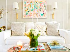 a white sofa with printed pillows, scones & modern art