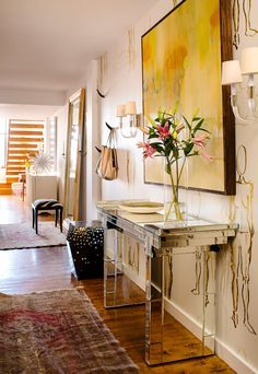Console table in hallway of loft with yellow art and pretty flowers