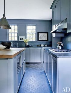 The kitchen features a honed-stone backsplash and counters, a Thermador cooktop, and a Brazilian-slate floor