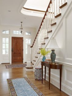 Traditional home foyer w/ white wood paneling, gorgeous staircase & solid wood front door.