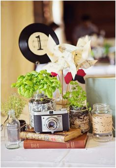 Vintage wedding table decorations. The mason jar with sheet music, the old books and camera, etc.
