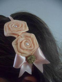 Tiara de metal forrada com fita de cetim, não aperta a cabeça, flores e laço de fita de cetim. R$ 12,00