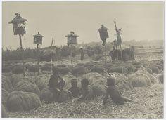 Jonge jongens spelen in een padi veld met geestenhuisjes waar gewerkt wordt aan de oogst, anoniem, 1890 - 1915