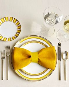 This bow tie napkin fold will add a fun pop to your table decor. Fold your napkin so the two halves meet in the middle. Fold it again, the same way as before, making a long strip. Fold the ends…Read more › Bow Tie Napkins, How To Fold Napkins, Linen Napkins, Cloth Napkins, Place Settings, Table Settings, Wedding Decorations, Table Decorations